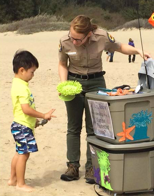 An interpreter explains marine life to a child